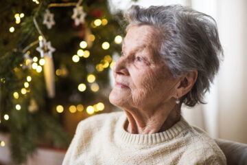featured image showing A portrait of a senior woman in wheelchair at home at Christmas time